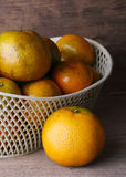 Orange fruit in white basket on wood table Stock Photos