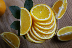 Orange fruit wooden background. Ripe fresh juicy oranges sliced on a glass plate Royalty Free Stock Images