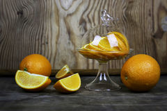 Orange fruit wooden background. Ripe fresh juicy oranges sliced on a glass plate Royalty Free Stock Photos