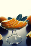 Orange fruit wooden background. Ripe fresh juicy oranges sliced on a glass plate Stock Images