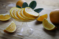 Orange fruit wooden background. Ripe fresh juicy oranges sliced on a glass plate Royalty Free Stock Photo