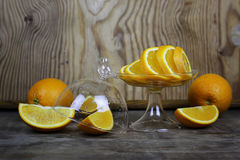 Orange fruit wooden background. Ripe fresh juicy oranges sliced on a glass plate Stock Photography