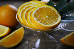 Orange fruit wooden background. Ripe fresh juicy oranges sliced on a glass plate Stock Photos