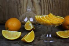 Orange fruit wooden background. Ripe fresh juicy oranges sliced on a glass plate Royalty Free Stock Image