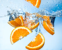 Orange fruits fall deeply under water with splash Royalty Free Stock Image