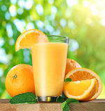 Orange fruits and glass of orange juice. Orange fruits and glass of orange juice on wooden table Royalty Free Stock Photo