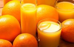 Orange fruits and juice. Glasses of  juice  and orange fruits Stock Photos