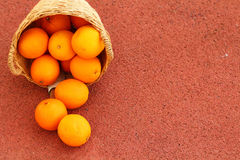 Orange fruits in wicker basket. Oranges fruits in wicker basket on Rubber floor Royalty Free Stock Photo