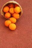 Orange fruits in wicker basket. Oranges fruits in wicker basket on Rubber floor Stock Photo