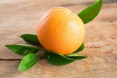 Orange frukt med sidor på träbakgrund Arkivfoton