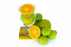 Orange frukt på magasinet och i klart exponeringsglas Arkivbild