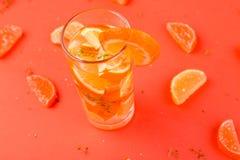 Orange fruktcoctail, detoxvatten på orange bakgrund Arkivfoton