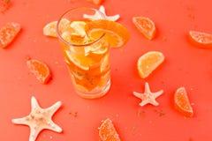 Orange fruktcoctail, detoxvatten på orange bakgrund Royaltyfri Fotografi