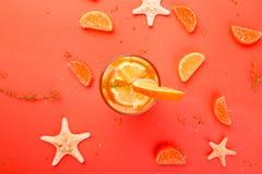 Orange fruktcoctail, detoxvatten på orange bakgrund Fotografering för Bildbyråer