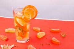 Orange fruktcoctail, detoxvatten på orange bakgrund unga vuxen människa Arkivbilder