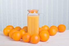 Orange fruktsaft bredvid läckra mogna apelsiner på tabellen Arkivfoto