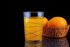 Orange fruktsaft - exponeringsglas med apelsiner på svart bakgrund Royaltyfri Fotografi