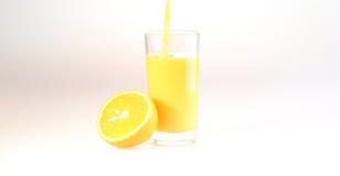 Orange fruktsaft flöden för en ström i ett genomskinligt exponeringsglas, ett exponeringsglas med Fotografering för Bildbyråer