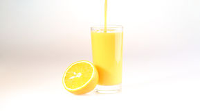 Orange fruktsaft flöden för en ström i ett genomskinligt exponeringsglas, ett exponeringsglas med Arkivbilder