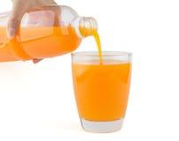 Orange fruktsaft hällde från flaskan till ett exponeringsglas Royaltyfri Fotografi