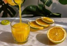 Orange fruktsaft hälls från en flaska in i ett exponeringsglas Royaltyfria Bilder