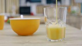 Orange fruktsaft hälls in i ett exponeringsglas Förberedelse av frukostnärbildsikten stock video