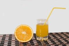 Orange fruktsaft i ett exponeringsglas och en apelsin Royaltyfri Foto
