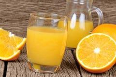 Orange fruktsaft i ett exponeringsglas och en kanna på tabellen Arkivbild