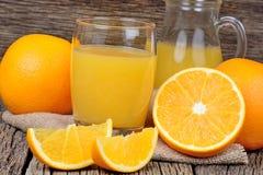 Orange fruktsaft i ett exponeringsglas och en kanna på tabellen Royaltyfri Foto