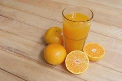 Orange fruktsaft i ett exponeringsglas och en ny frukt Arkivbild