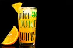 Orange fruktsaft i ett exponeringsglas p? en svart bakgrund royaltyfria foton
