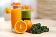 Orange fruktsaft i ett högväxt exponeringsglas med apelsinen och grönkål Fotografering för Bildbyråer