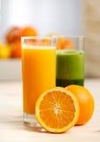 Orange fruktsaft i ett högväxt exponeringsglas med en halv apelsin Royaltyfria Bilder