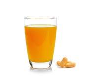 Orange fruktsaft i exponeringsglas med minnestavlan för vitamin c på vit bakgrund Arkivbild