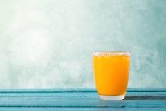 Orange fruktsaft i exponeringsglas med is på tid för sommar för havblått trä Arkivbilder