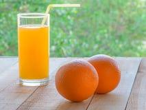 Orange fruktsaft i exponeringsglas och apelsiner på en trätabell vid fönstret Royaltyfri Foto