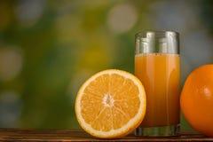 Orange fruktsaft i exponeringsglas och apelsiner på naturlig grön bakgrund Arkivfoto