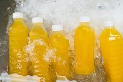 Orange fruktsaft i flaskor på till salu skärm Arkivfoto
