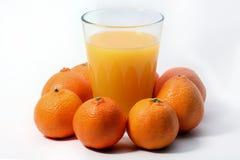 Orange fruktsaft med apelsiner omkring Arkivbilder