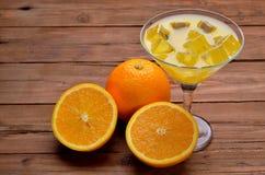 Orange fruktsaft med is i ett exponeringsglas av martini på en trätabell Royaltyfria Foton