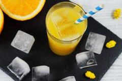 Orange fruktsaft med is på svartvit bakgrund Fotografering för Bildbyråer