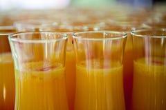 Orange fruktsaft med röd likör i högväxta exponeringsglas på ett magasin royaltyfria bilder