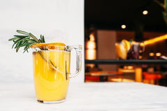 Orange fruktsaft med rosmarin på kafébakgrund Royaltyfria Foton