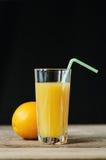 Orange fruktsaft med sugrör Arkivfoto