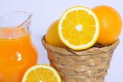 Orange fruktsaft och apelsin på vit bakgrund Arkivfoto