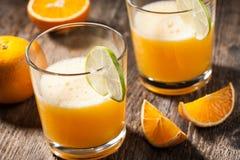 Orange fruktsaft och apelsiner Arkivbild