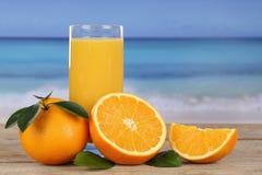 Orange fruktsaft och apelsiner på stranden Arkivfoto