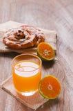 Orange fruktsaft och kanelbrun rulle för russin Arkivbild