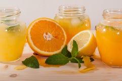 Orange fruktsaft och lemonad med mintkaramellen i krus Arkivbild