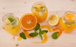 Orange fruktsaft och lemonad med mintkaramellen i krus Royaltyfria Foton